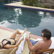 Couple having cocktails next to swimming pool — Foto Stock