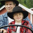 Stock Photo: Father and son driving tractor