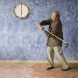 Senior man swinging at clock with golf club — Stock Photo