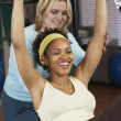 African woman exercising with personal trainer — Stockfoto