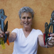 Senior woman holding handfuls of tools - Stock Photo