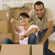 Man pushing wife in moving box — Stock Photo