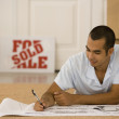 Man writing on blueprints in new house — Stock Photo