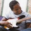 African man playing guitar on sofa - Stock Photo
