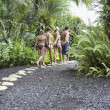 Family walking on tropical path — ストック写真