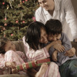 Hispanic family hugging on Christmas — Stock Photo