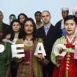 Multi-ethnic holding the word PEACE — Stock Photo