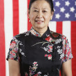 Senior Asian woman standing in front of American flag — Stockfoto