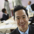 Asian businessman with coworkers in background — Stock Photo