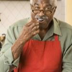Senior African man eating fruit — Stock Photo #23278534