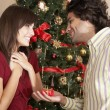Hispanic man giving girlfriend Christmas gift — Stock Photo #23278546