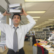 Hispanic businessman holding binders on head — Stock Photo