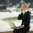 Hispanic businesswoman talking on cell phone — Stock Photo