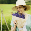 Stock Photo: Womsmelling bouquet of flowers