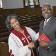 African American female Reverend shaking hands with parishioner — Stock Photo