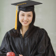 Asian woman wearing graduation cap and gown — Stock Photo