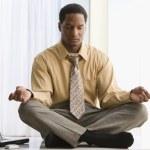 African American businessman meditating on desk — Stock Photo