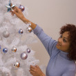 African woman hanging Christmas ornament — Stock Photo