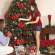 Couple decorating Christmas tree — Stock Photo