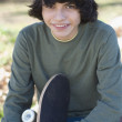 Hispanic boy holding skateboard — Stock Photo