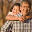 Hispanic father giving daughter piggyback ride — Stock Photo