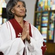 African American female Reverend praying - 图库照片