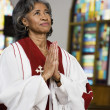 African American female Reverend praying — Stock Photo