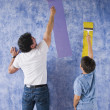 Hispanic father and son painting wall - Stock Photo