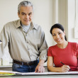 Hispanic male and female architects with blueprints — Stock Photo