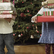 Hispanic brother and sister holding Christmas gifts — Stock Photo