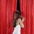 Hispanic beauty queen peeking through curtains — Foto de Stock