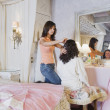 Hispanic girl having hair brushed in bedroom — Stok fotoğraf