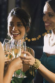 Multi-ethnic women toasting with champagne — Stock Photo