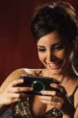 Middle Eastern woman playing hand held video game — Stock Photo