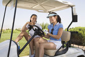 Portrait of two women in golf cart — Стоковое фото