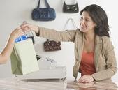 Hispanic klerk aankoop overhandigen aan klant in boutique — Stockfoto