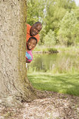 African grandfather and grandson peeking out from behind tree in park — Stock Photo