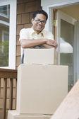 Homem asiático, apoiando-se em caixas de mudança na varanda — Foto Stock