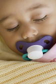 Close up of Hispanic baby sleeping with pacifier — Stock Photo