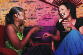 Dos mujeres africanas con cócteles y riendo — Foto de Stock