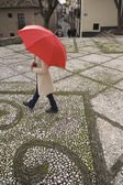 High angle view of woman walking with umbrella in urban setting — Stock Photo