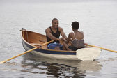 African couple smiling in row boat — Zdjęcie stockowe