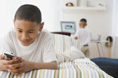 Indian boy looking at cell phone on bed — Stock Photo