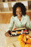 African woman eating sushi at home — Stock fotografie