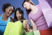 Three woman looking in shopping bags — Stock Photo