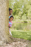 African sister and brother peeking out from behind tree in park — Stock Photo