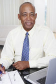 Senior African businessman with laptop at desk — Stock Photo