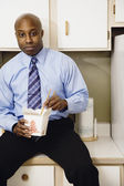 African man eating take out food in kitchen — Stock Photo