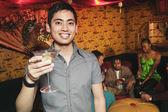 Pacific Islander man holding cocktail at nightclub — Stock Photo