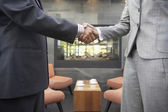 Businesspeople shaking hands in cafe — Stock Photo